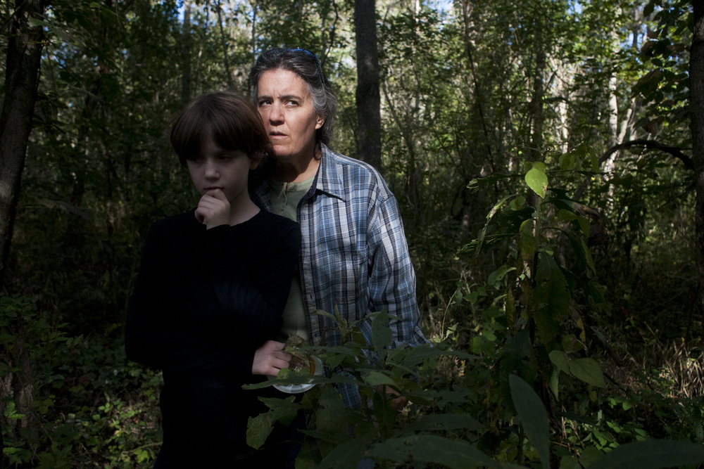"Ronda Clark and her daughter Corral hike through the forest on their 60-acres of land. ""We're supposed to be stewards of the land and be part of cycle inside of separating from it or being above it,"" said Ronda."