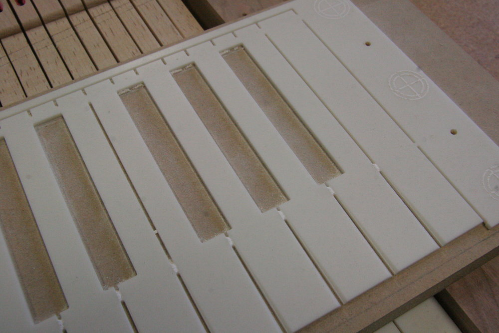 Naturals are machined from solid surface countertop materials.  This photo shows blank after CNC machining leaving tabs and registration pin holes behind sharps to aid in placement on keyboard blank.