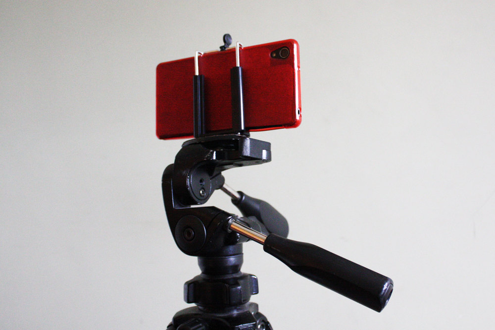 A phone mounted on a photographic tripod