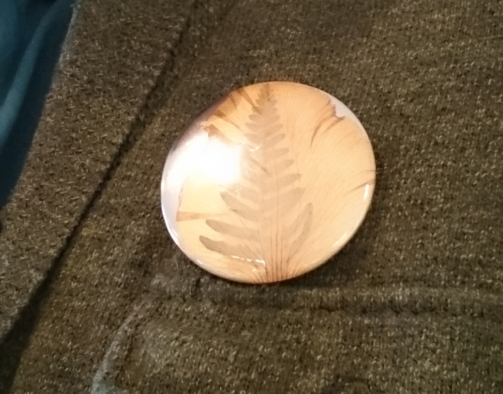 A handmade badge using a fern and translucent petal