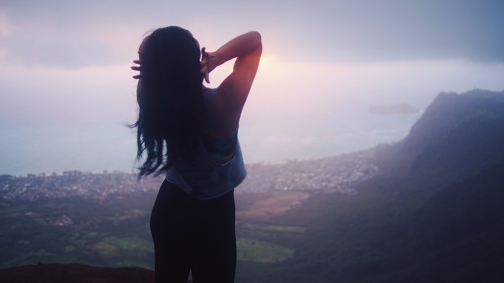 Sillhouette of a girl on a mountain at sunrise