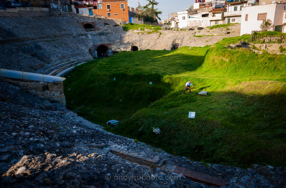 A gardener tends to the grass in Durrës Amphitheater