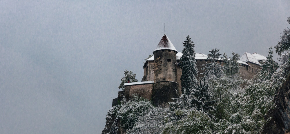 Castle Bled stands watch over Lake Bled in a winter storm