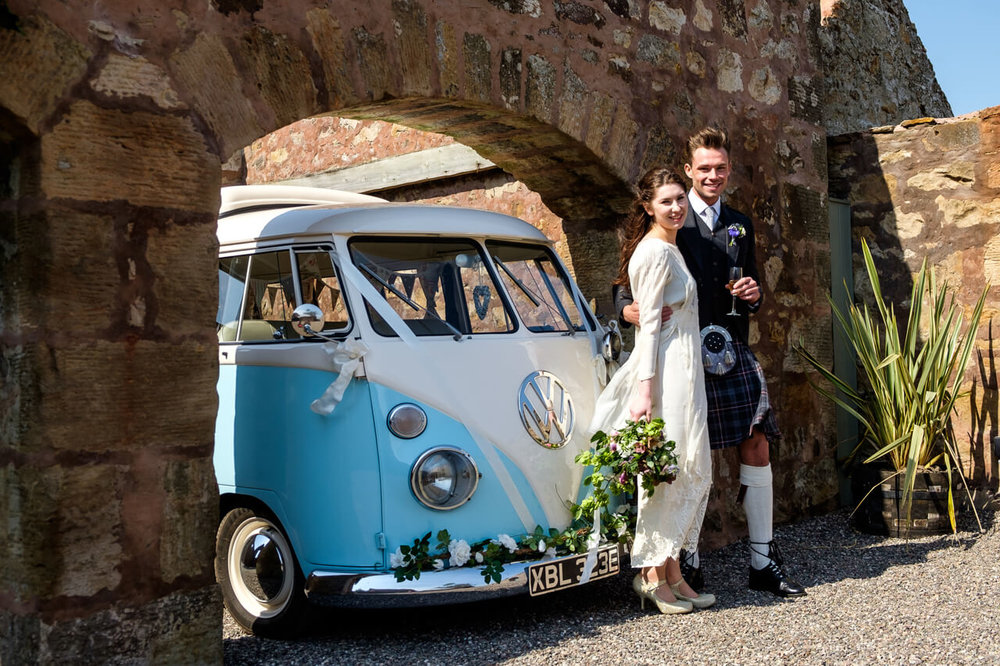 Our VW camper wedding car under an arch at the Cow Shed Crail with a couple standing in front