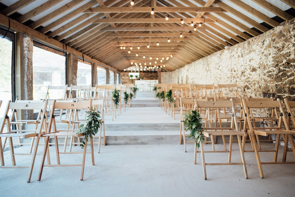 The inside of the Cowyard Barn rustic party and reception space set for a wedding ceremony at Pengenna Manor Cornwall wedding venue01.jpg
