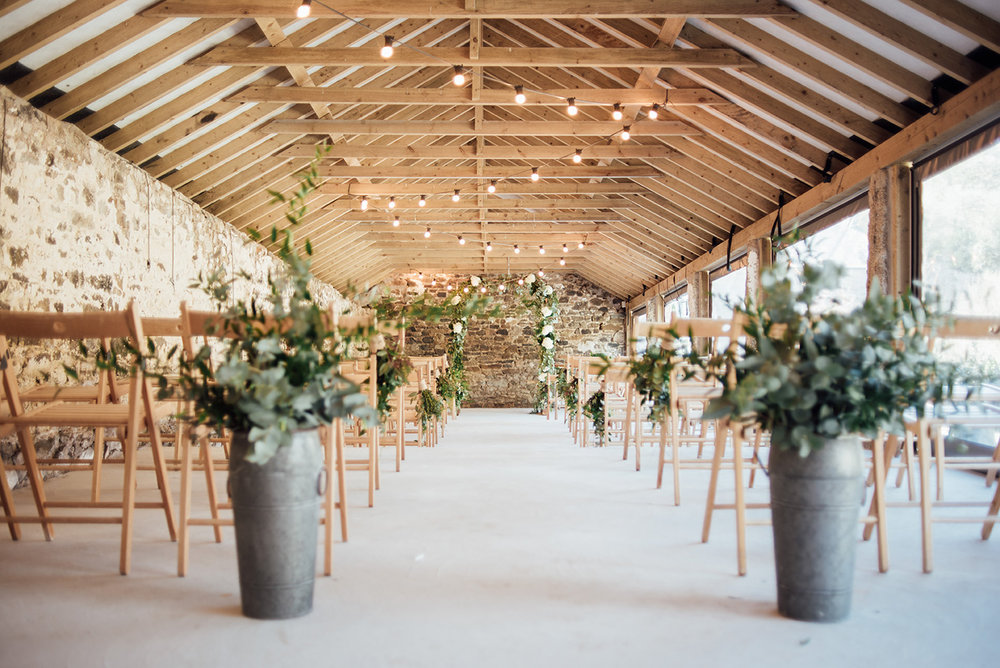 The inside of the Cowyard Barn rustic party and reception space set for a wedding ceremony at Pengenna Manor Cornwall wedding venue.jpg
