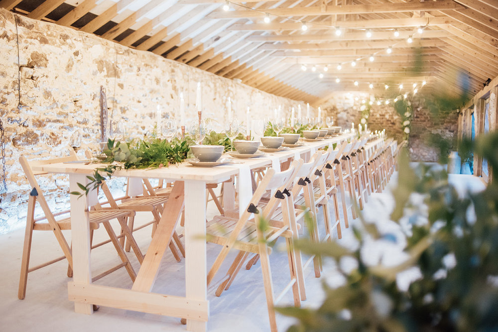 The inside of the Cowyard Barn rustic party and reception space set for a night time dinner at Pengenna Manor Cornwall wedding venue02.jpg
