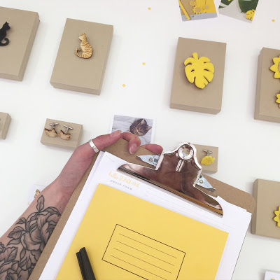 Birds eye view of laser cut jewellery and yellow notepad