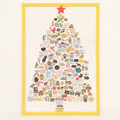 Cork board full of enamel pins in the shape of a Christmas Tree