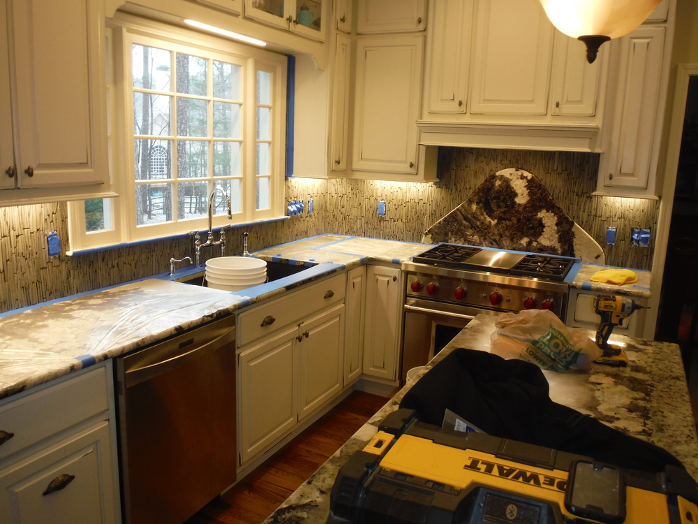 """A custom backsplash install. We recessed that 100lb pound of granite into the wall behind the stove. The homeowner called it her """"mountain"""""""