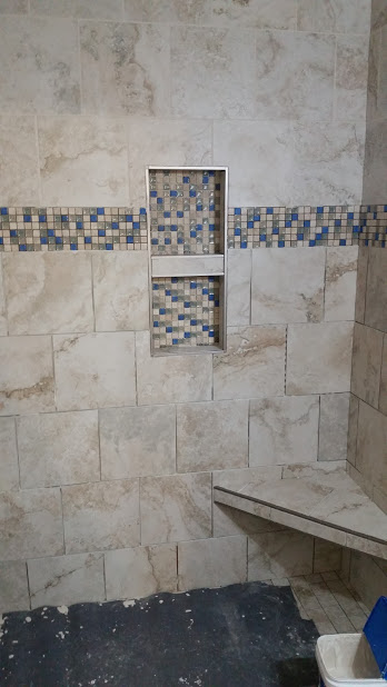 Had to use blue tape to cover these mosaic pieces because when grout gets into the crevices, it won't come out! I used Mapei's Flex color single component grout and it will look the same in 10 years as when I left. The other bid is cheaper because they are not using high end grout.