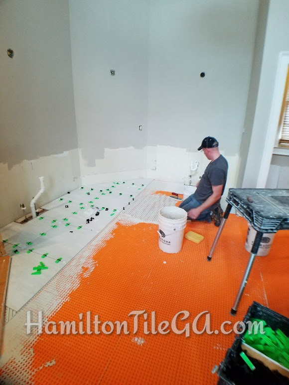 """Ditra by Schluter Systems taking the place of cement board as our uncoupling layer. This plastic product is set into a bed of latex thin set. The waffles act as tiny pillars holding up your tile. Ask your installer, """"What is the purpose of this layer?"""""""