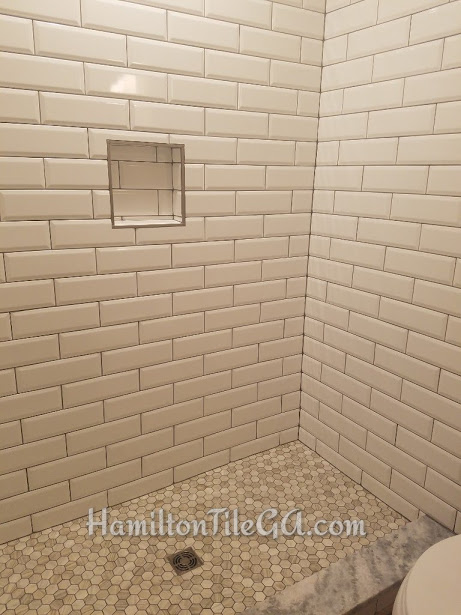 This one is a beveled tile shower. A very bold look. We have hex wood look tile on the floor with a hard surface curb matching the top on the vanity. This is a 12x12 soap niche edged with Quadec brushed nickle profiles. Tile purchased at Traditions in Alpharetta.