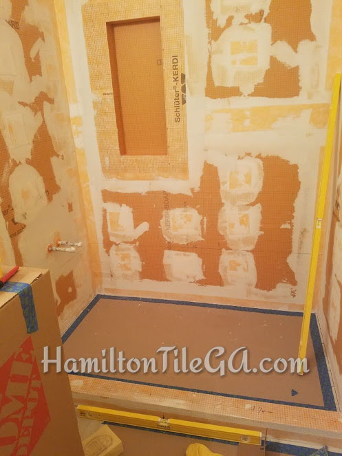 A water proofed Kerdi shower ready for tile. With this system water stays on top of our fabric and is directed to the drain. This shower is vapor proof.    Watch this short video for an explanation of how a traditional shower system works compared to a Schluter shower.