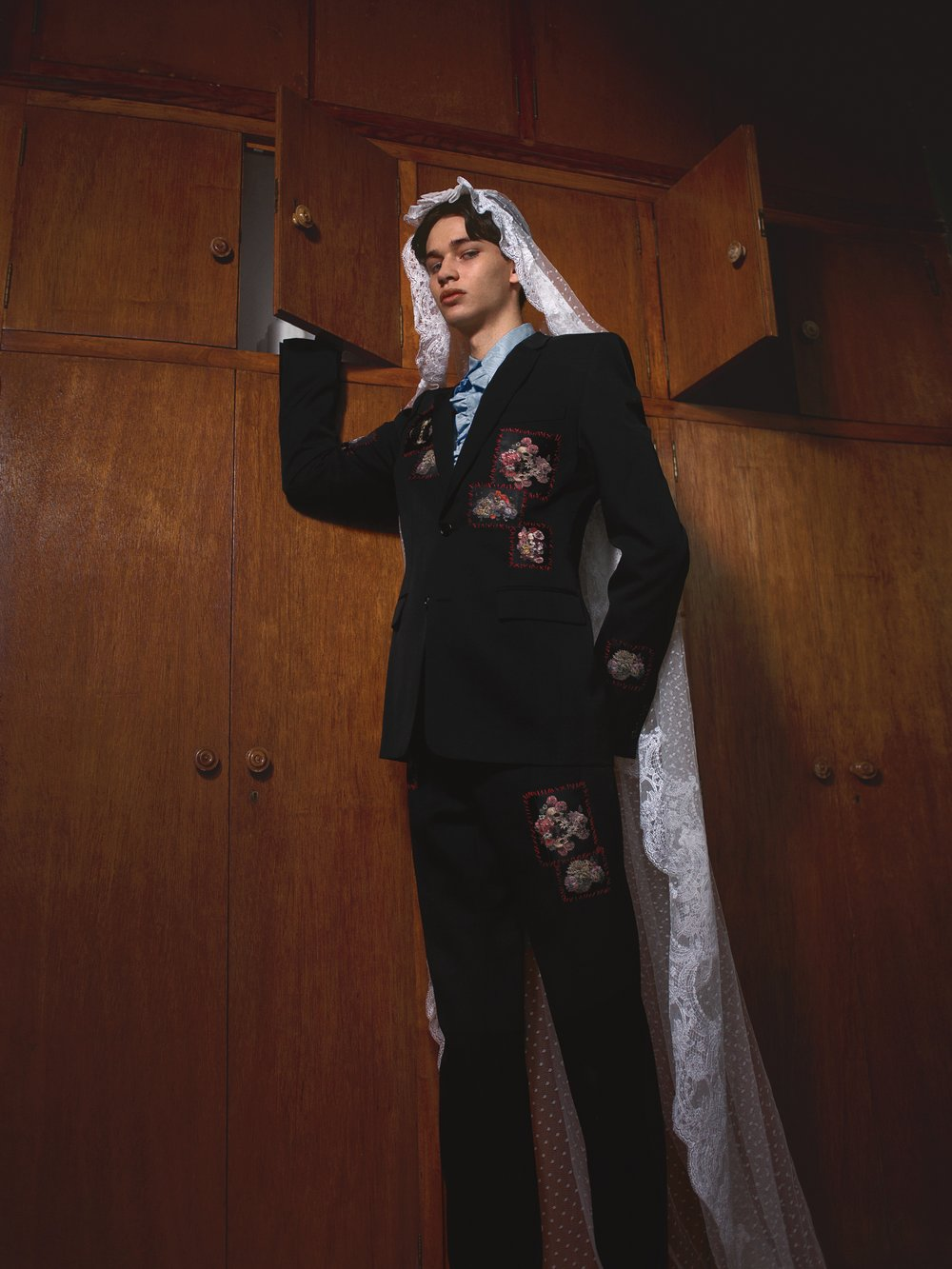 Nicolás viste traje de DIOR HOMME, camisa de PALOMO SPAIN y mantilla de LE PARISIÉN.