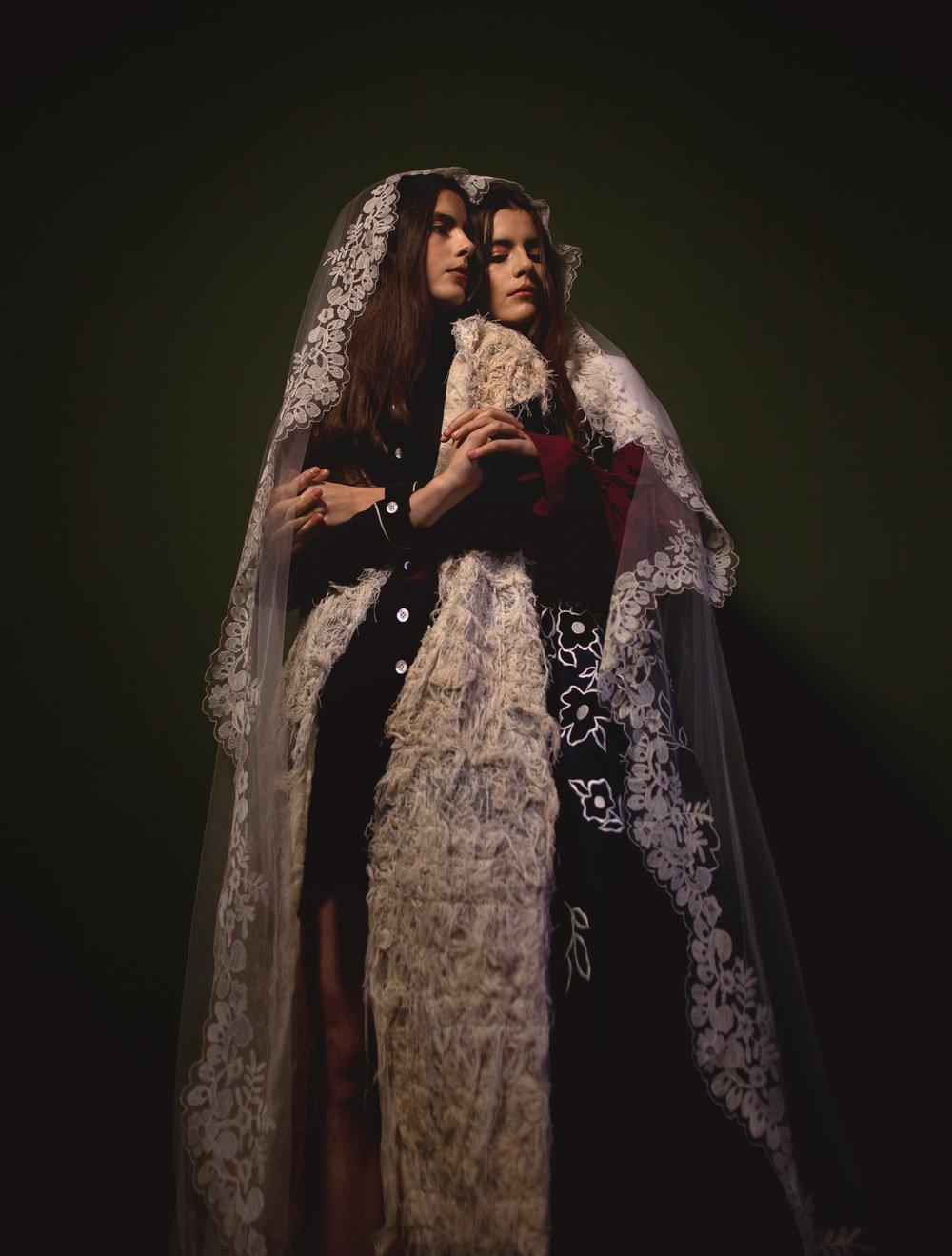 Virginia viste vestido de  MIU MIU  y chaleco de  ELA FIDALGO. Victoria viste vestido de  CAROLINA HERRERA  y camiseta de  MANÉMANÉ .Ambas con mantilla de  LA PARISIÉN.