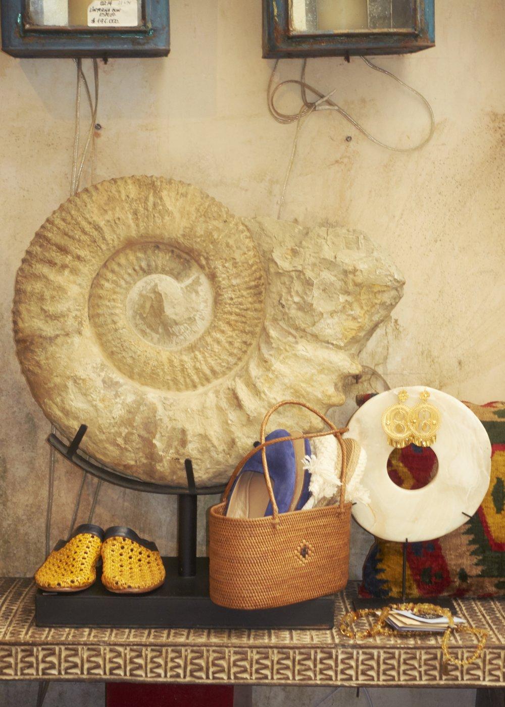 """Zapatos tejidos de  CECILIA BRINGHELI,  zapatos azules de  SOLOVIERE , disco blanco """"de ballena"""" hecho en Bali disponible en  CASA CHIQUI , bolso pequeño tipo cesta hecho en Indonesia disponible en  CASA CHIQUI  y collar y aretes de  CASA CHIQUI."""