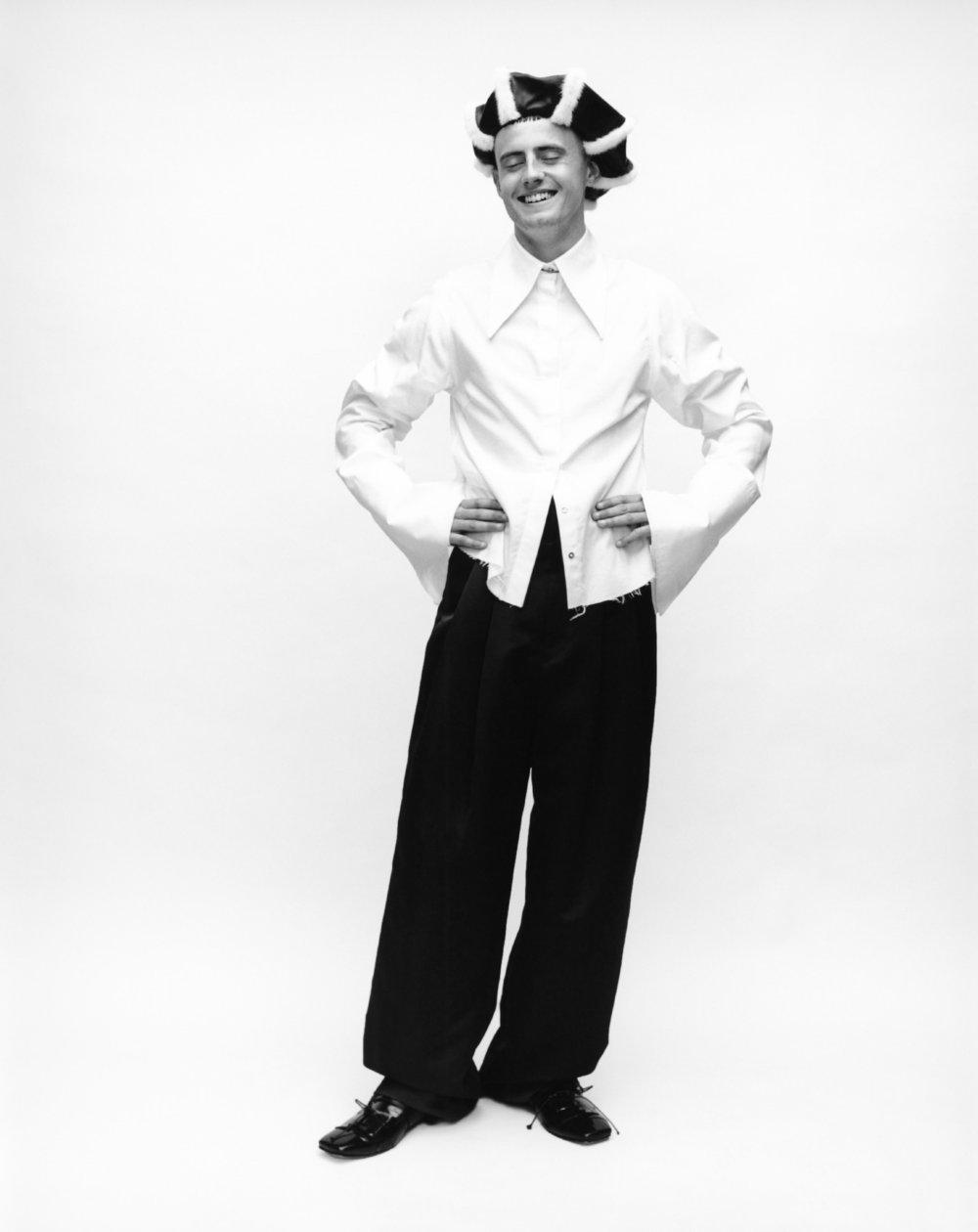 Cae viste camisa de  MARQUES ALMEIDA, pantalón de  WOOYOUNGMI, zapatos de  CHARLES JEFFREY LOVERBOY  y sombrero de  NOEL STEWART.