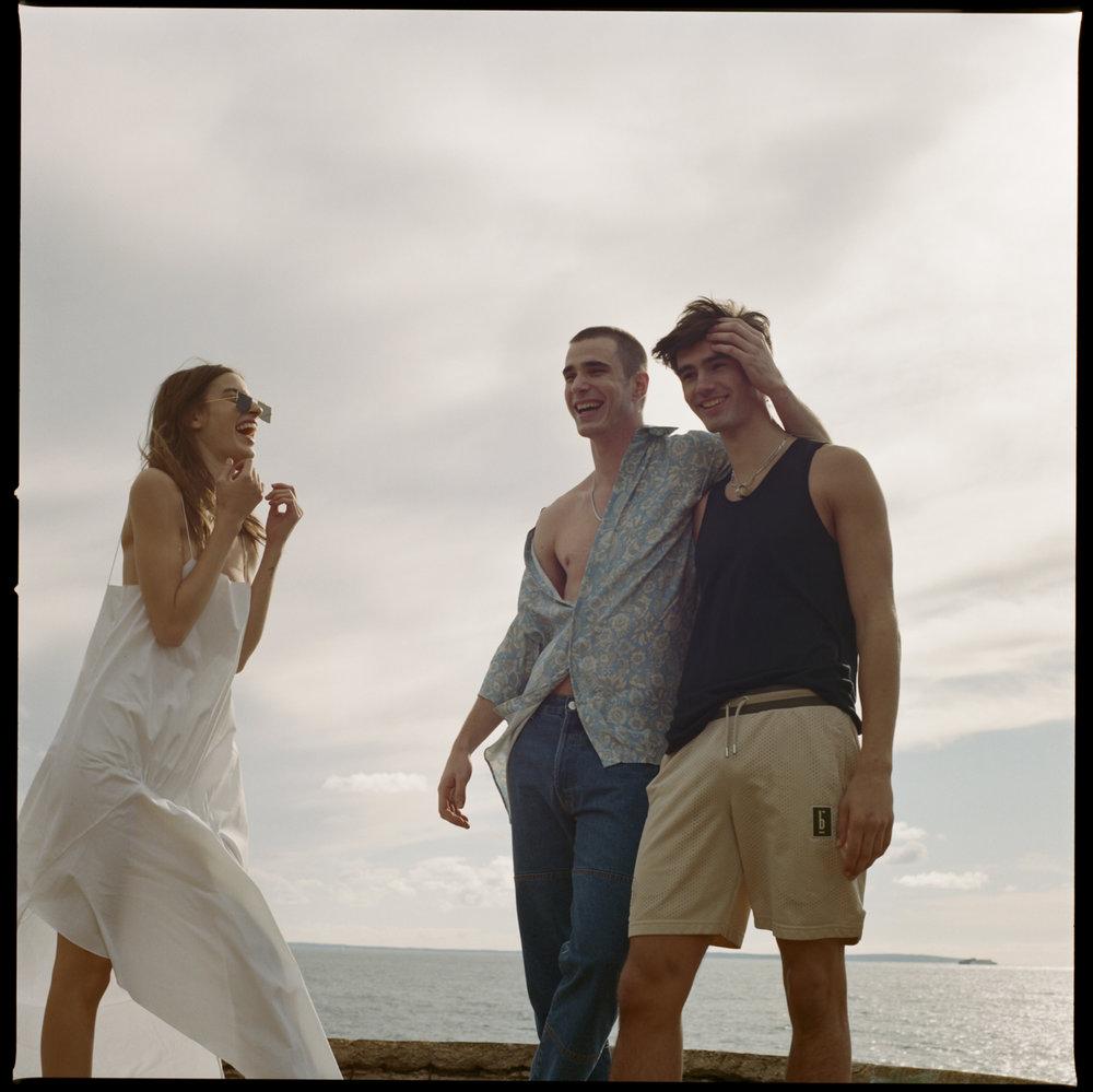 Marta con vestido de  ESTEBAN CORTÁZAR . Marc viste camisa de  DRIES VAN NOTEN y pantalón de  ÉTUDES . Mathias viste camiseta sin mangas de  BERLUTI y pantalón corto de  PIGALLE .