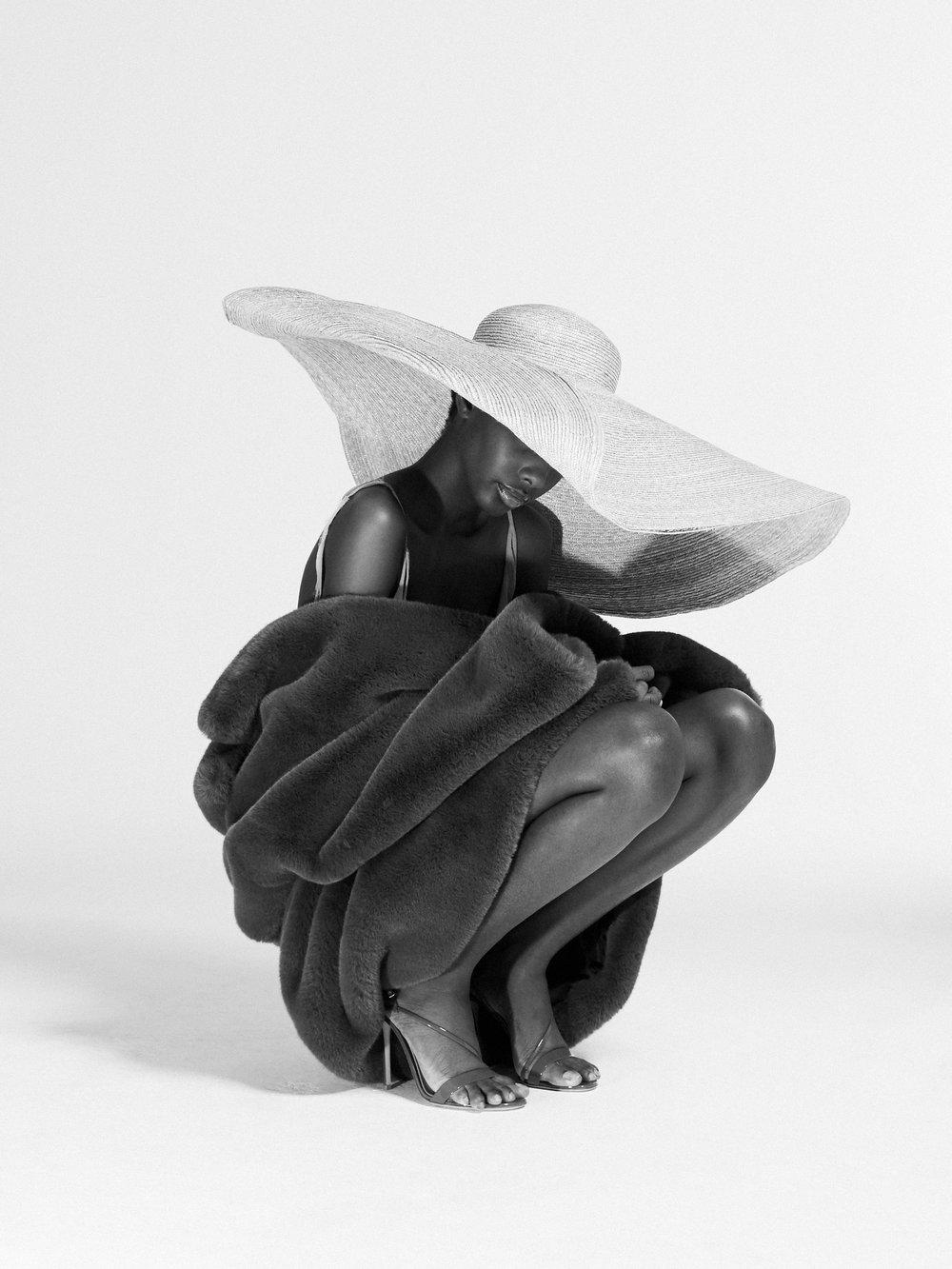 Sombrero y vestido de  JACQUEMUS , abrigo de  COURRÈGES  y zapatos de  GIANVITTO ROSSI.