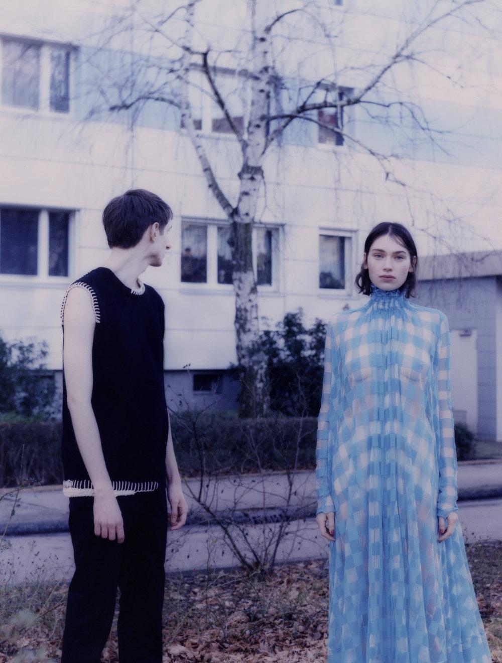 Rebecca con vestido de  JIL SANDER . Adrian viste top de  JIL SANDER  y pantalón de  HERMÈS .
