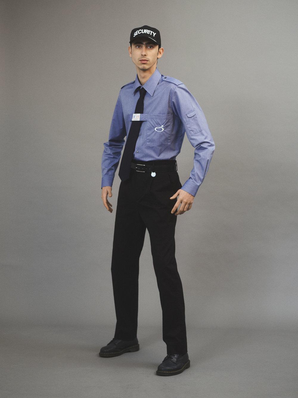 Camisa y pantalón de  XANDER ZHOU , corbata de  TIGER OF SWEDEN , cinturón de  HERMÈS , gorra de  WORKWEAR LONDON y botas de  DR. MARTENS .