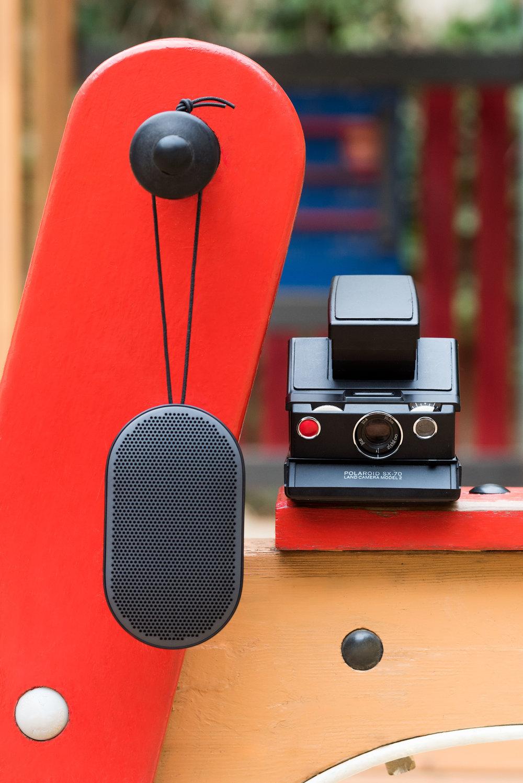 Bocinas de  BANG & OLUFSEN  y cámara fotográfica de  IMPOSSIBLE PROJECT.