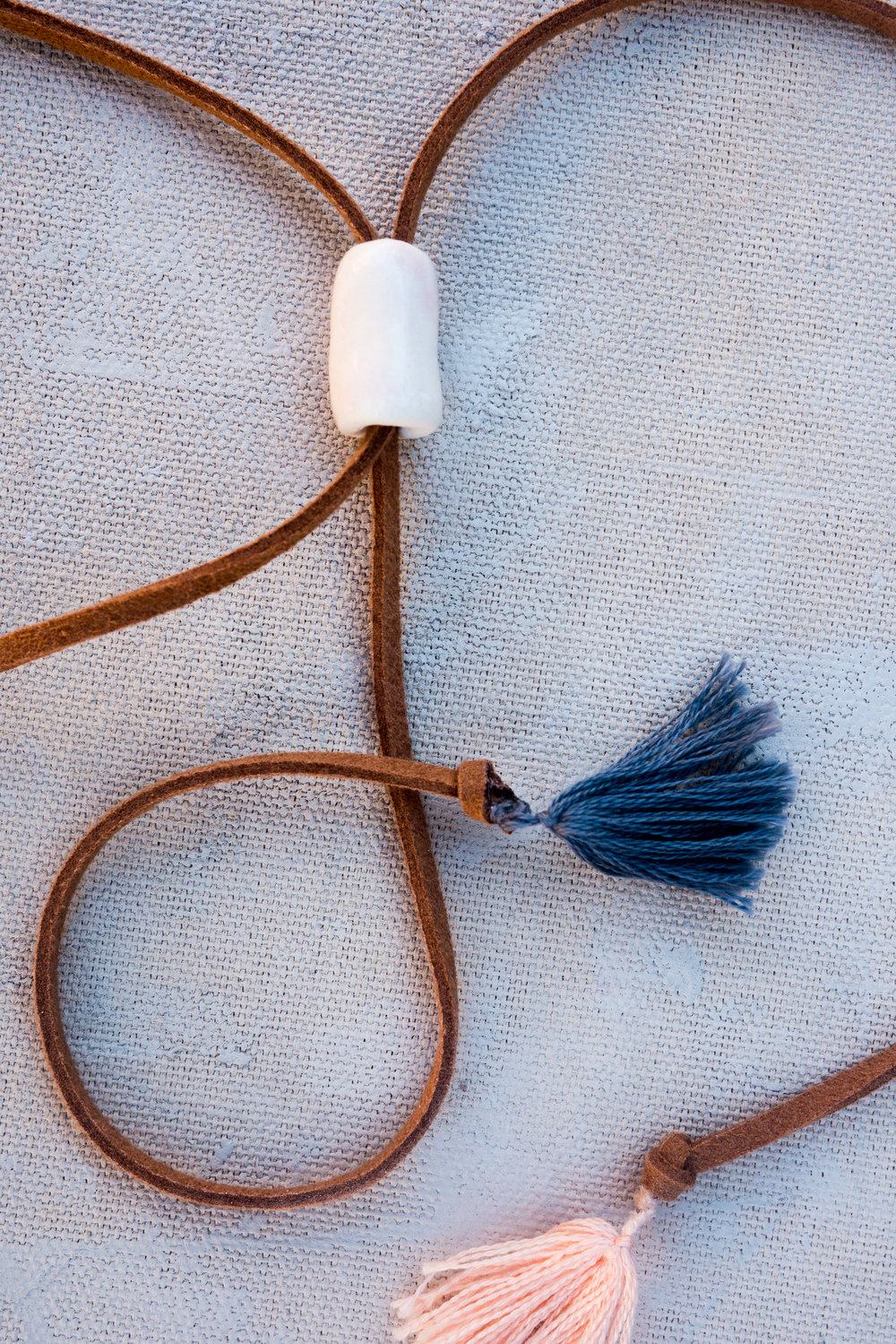 Vegan suede, a porcelain toggle bead, and cotton tassels on our Desert Moon necklace.