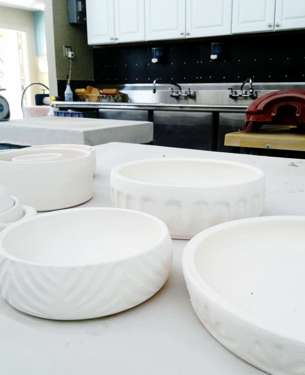 A collection of faceted and carved pottery bowls, cups, and mugs made in Austin, Texas, by Little Clay Studio.
