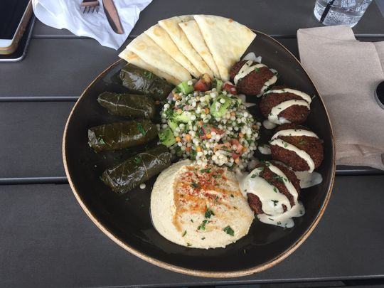 A sampler platter consisting of falafel, hummus, pita bread, couscous medley and stuffed grape leaves offered at Luna Grill Palm Desert. (Photo: Jose Bastidas/The Desert Sun)