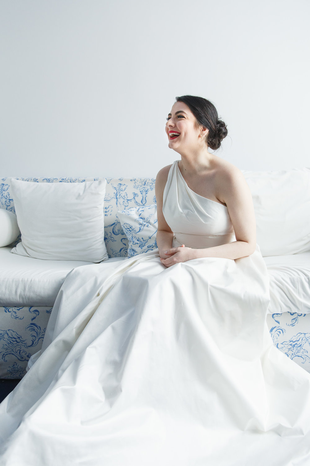 Bride laughs on a blue and white couch waiting to meet her soon-to-be husband for their first look.