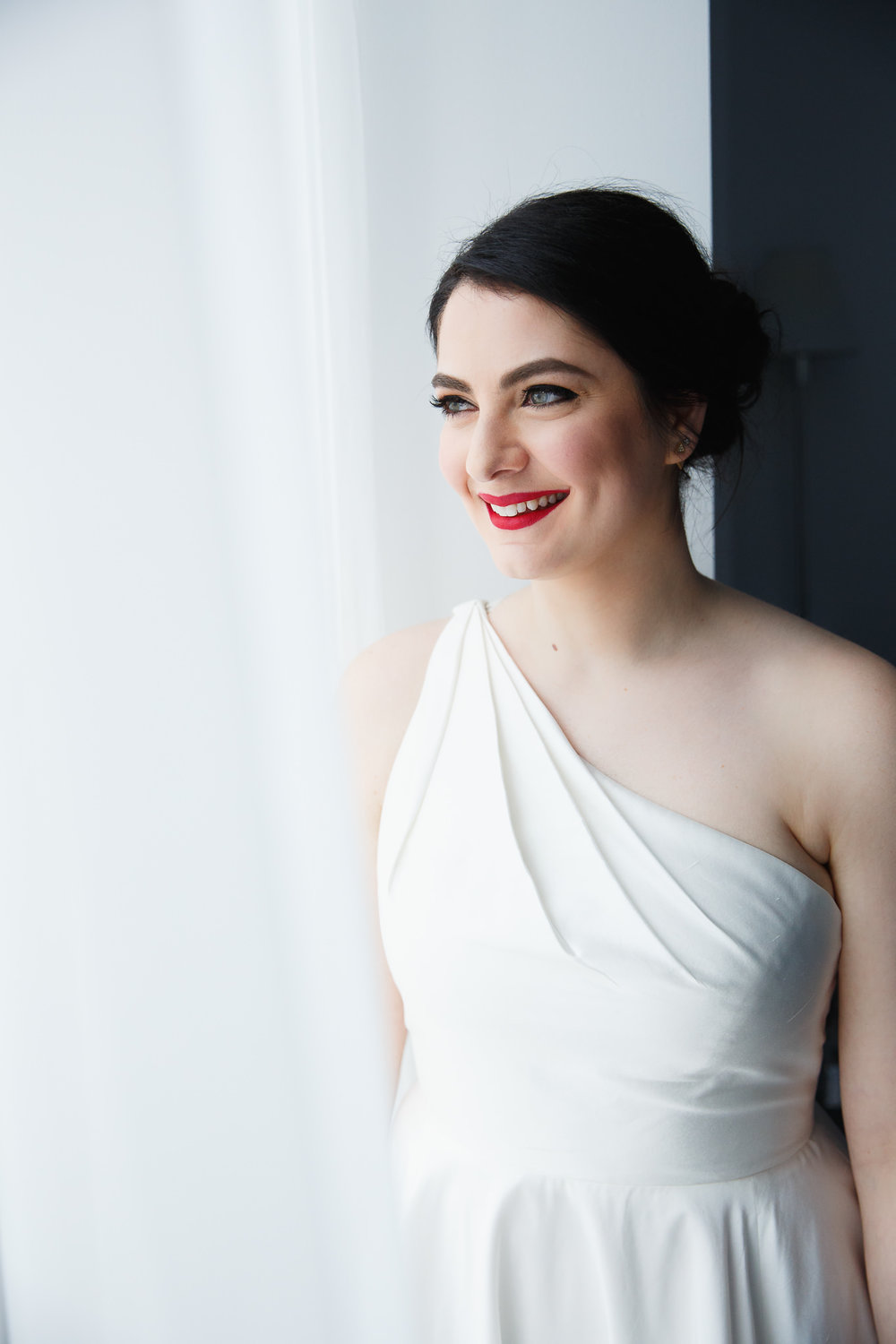 Bride in a one-shoulder dress with red lips looks out the window at the Nomo Soho hotel.