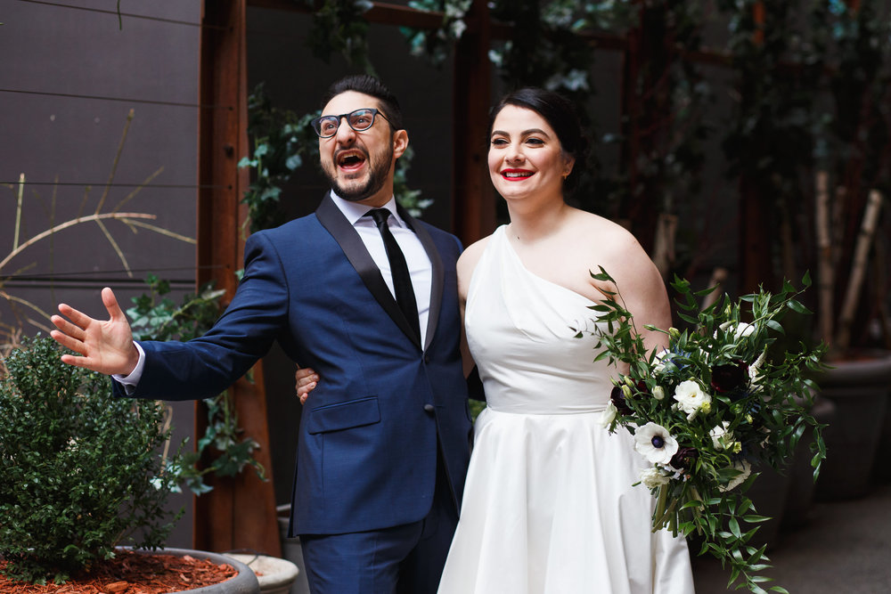 Groom in a blue and black suit is thrilled by seeing his bride at their first look in front of the Nomo Soho Hotel.