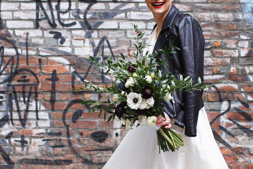 Bride shows off her flowers by Stems Brooklyn in front of the Nomo Soho hotel