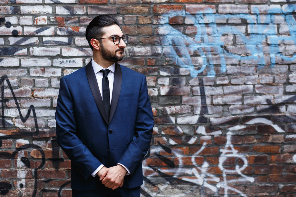 Groom in a blue and black tux in front of a graffiti wall in soho new york city