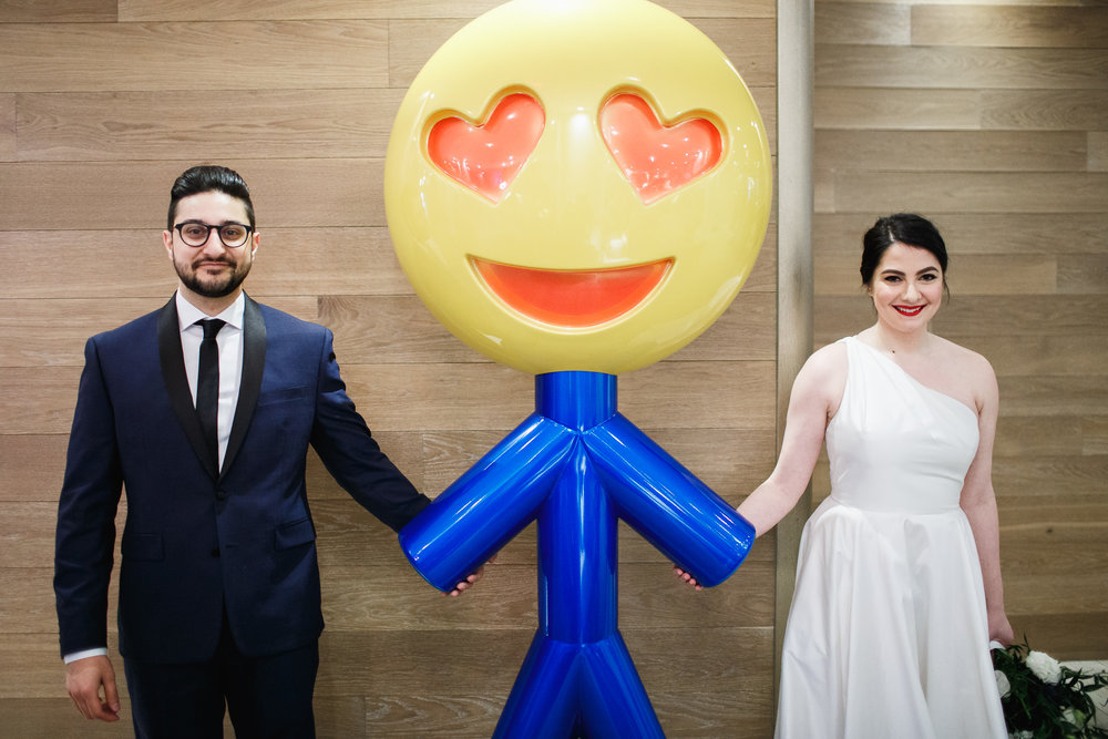 Bride and Groom pose with a giant emoji smiley face sculpture at the nomo soho hotel