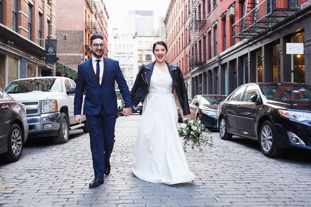 bride and groom walk down a brick street in soho new york city