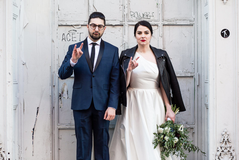 groom in a blue and black suit and bride in a white dress with a black leather jacket throw a rockstar sign