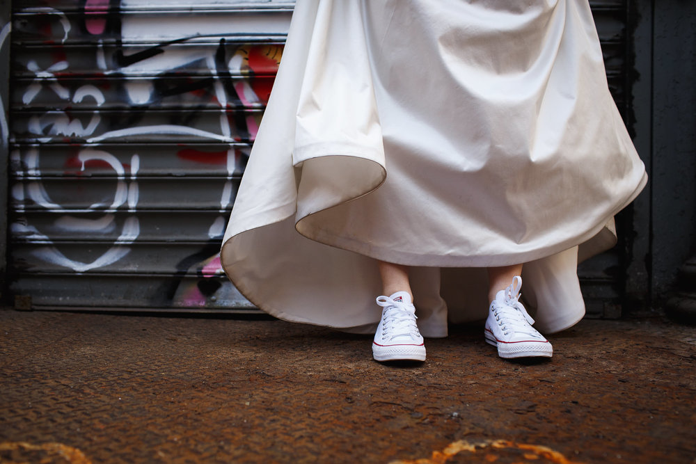Bride with white keds in front of a graffiti wall in soho new york city