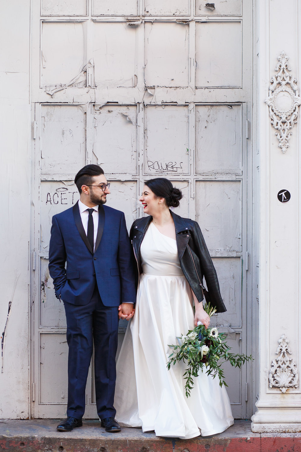 Bride and groom laugh in front of a painted white door in soho new york city with a stems brooklyn bouquet