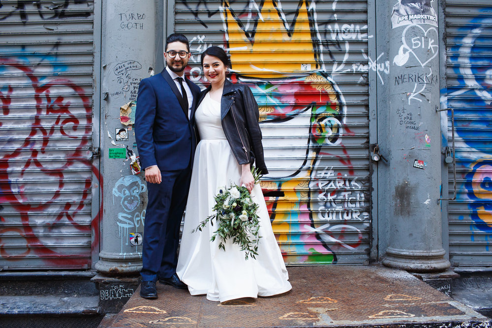 bride and groom in front of a graffiti wall in soho new york city