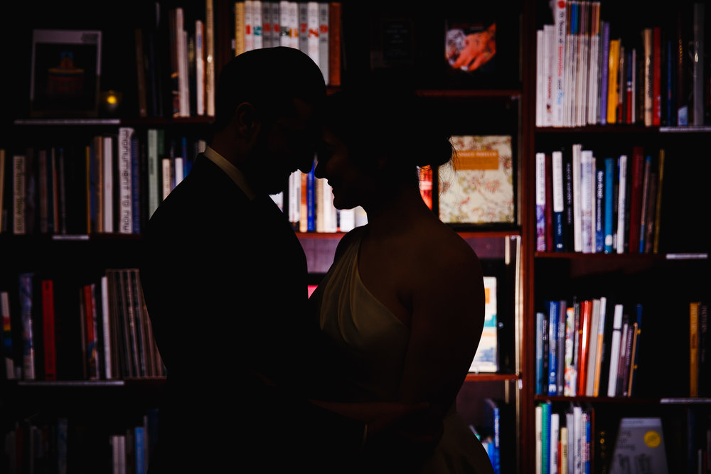 Silhouette of the bride and groom in front of the stacks at the Housing Works bookstore