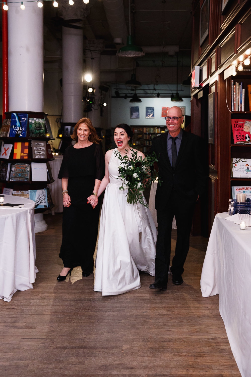 Bride being walked down the aisle by her parents at the Housing Works Bookstore