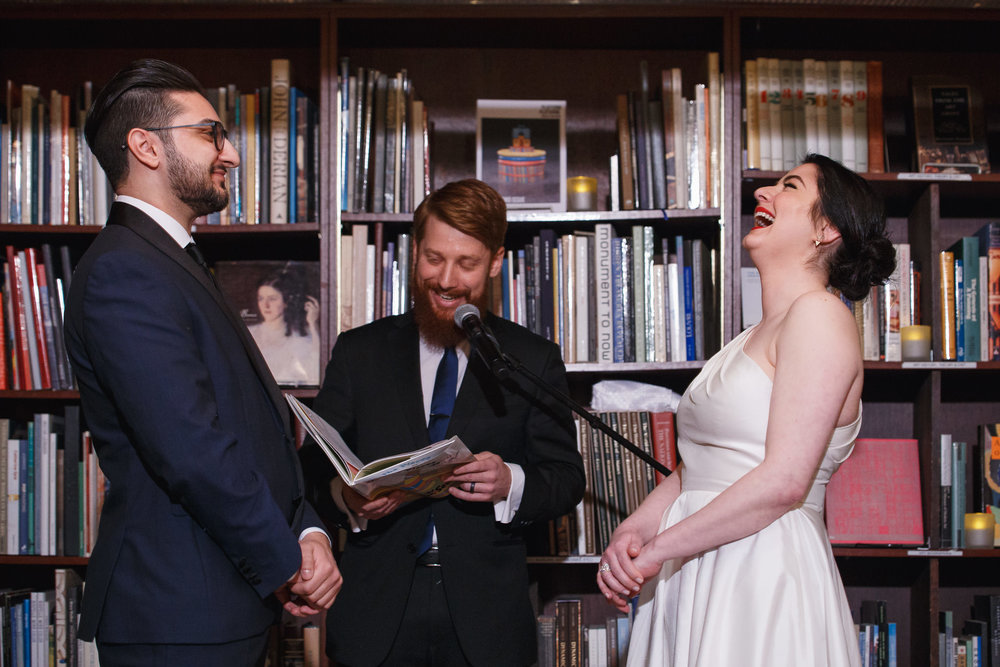 Bride and Groom laughing during their ceremony in the stacks during their Housing Works Bookstore Wedding