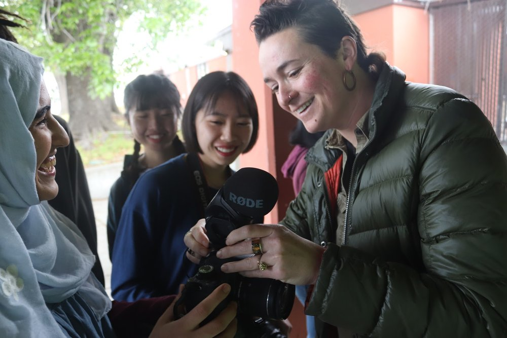 Mallory showing her students around a camera at Oakland International High School