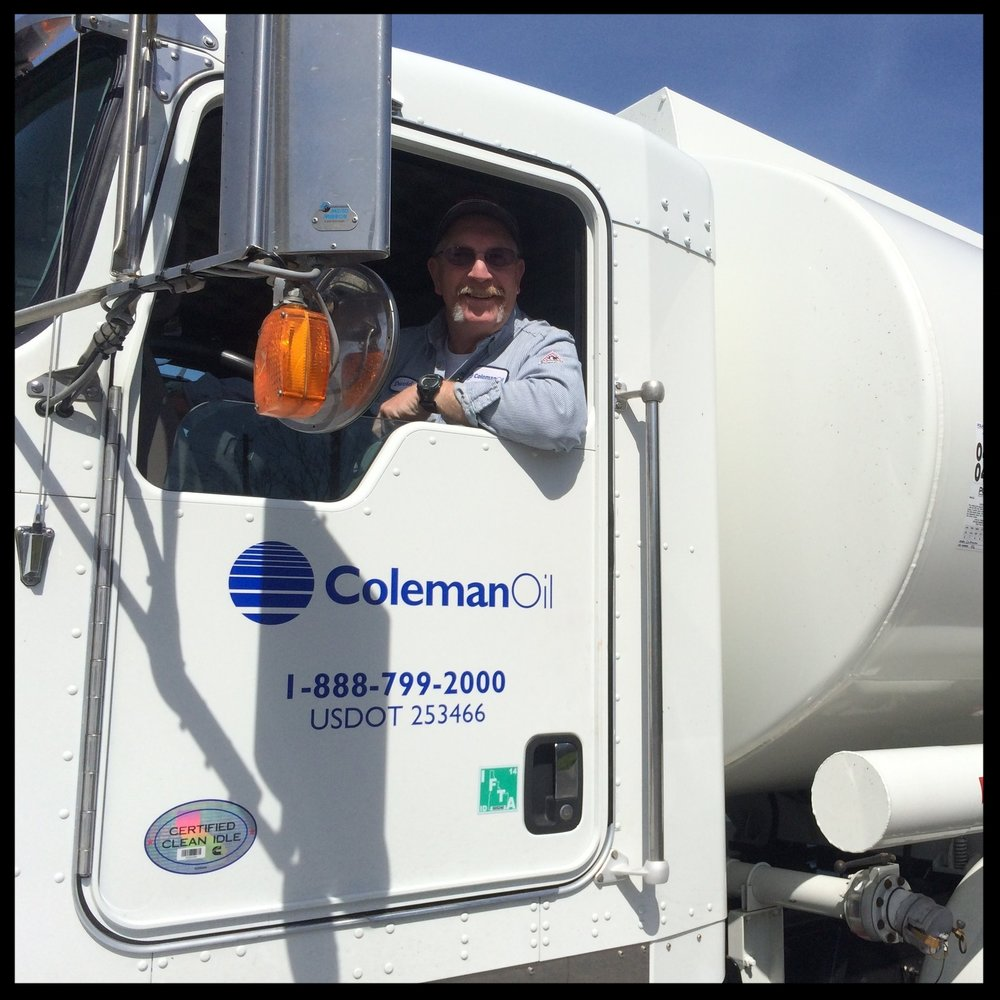 A friendly Coleman Oil driver smiles from the cab of his truck.