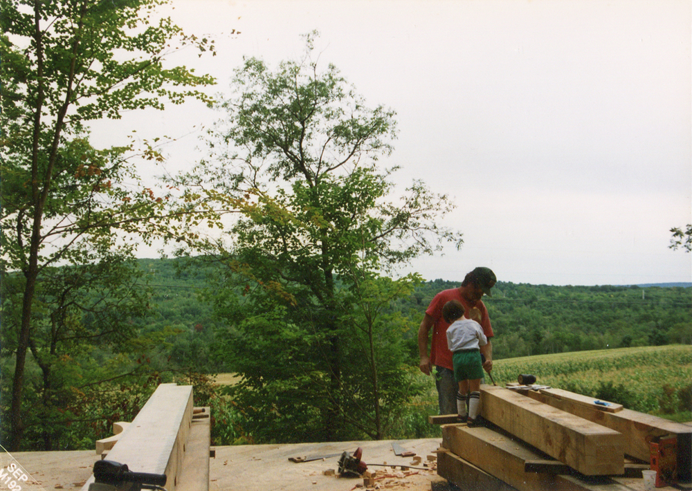 In 1992, Ben's parents moved the family and sawmill from Epping, New Hampshire to Monroe, cleared land, and began building a post-and-beam house of their own design.  Here, Zach, the youngest Block Brother, helps notch mortises in the pine beams.