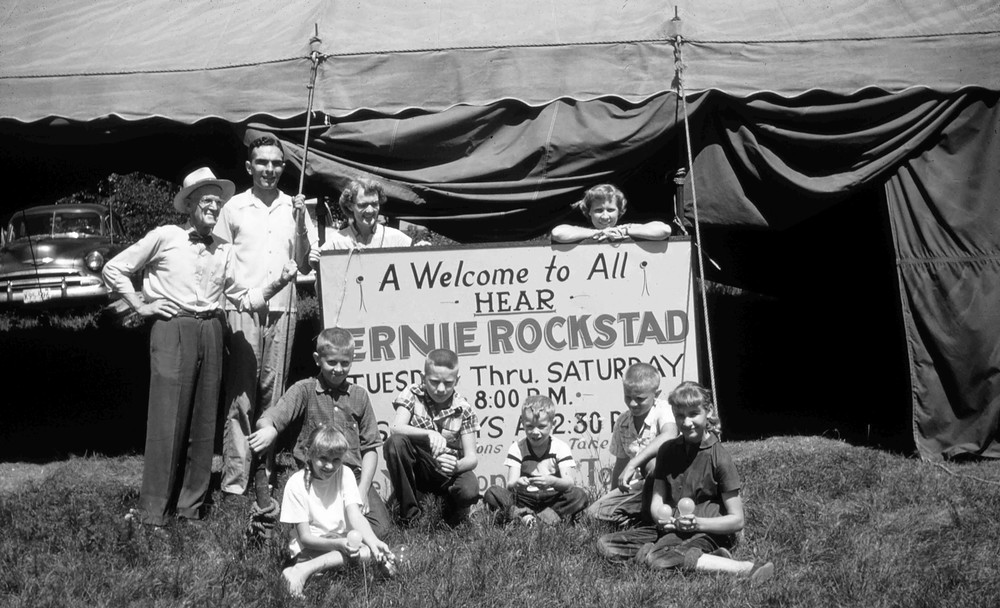 Family and friends gather around the old tent meeting sign.