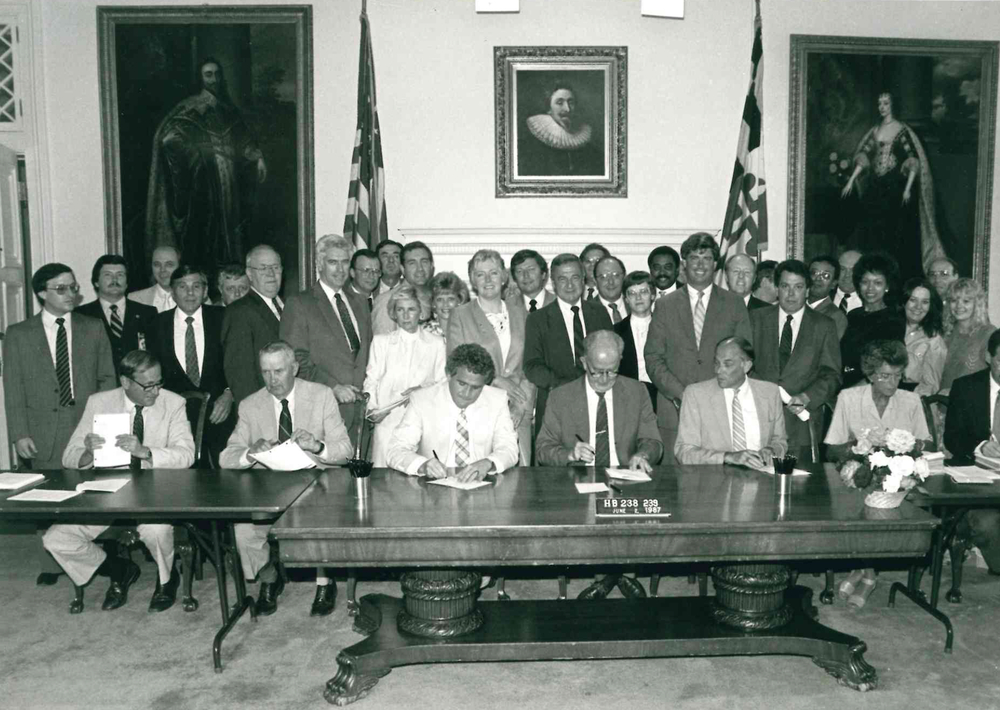 Click to zoom in. Michael Levin, pictured above at the far left at the signing of the Workers' Compensation Reform Act of 1987. Also seen above is Governor Schaefer seated fourth from the left, Senate President Mike Miller third from the left, and Speaker of the House Clay Mitchell seated fifth from the left.
