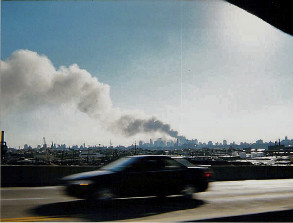 car speeding down highway with burning Towers in background after 9-11